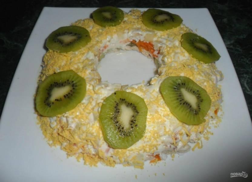 Остаётся только украсить салат. Обсыпьте его натёртым желтком, уложите дольки киви. Приятной дегустации!