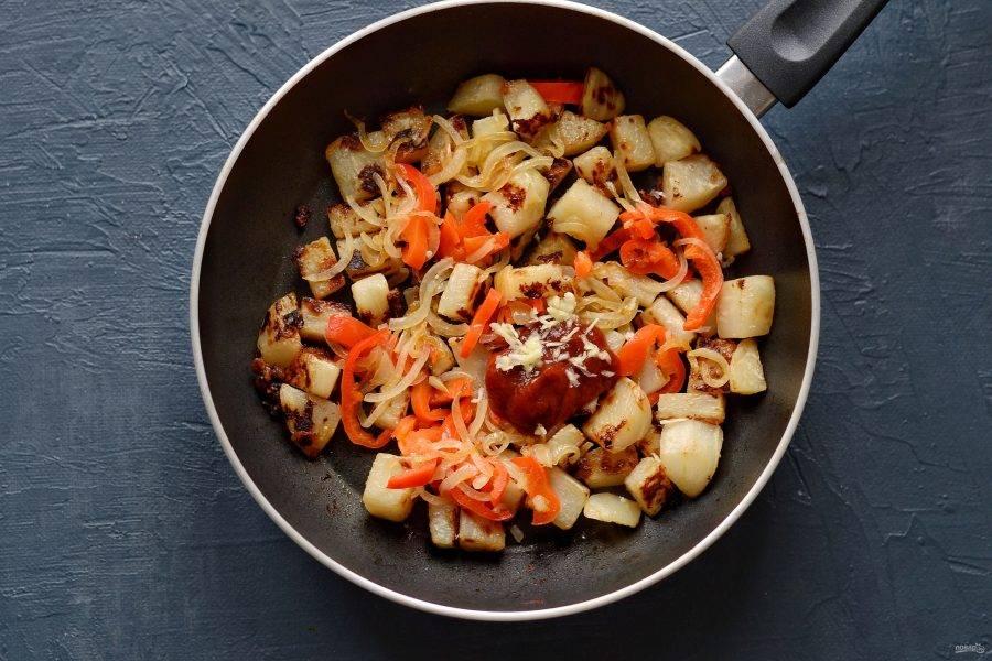 Выложите жареные овощи в сковороду. В конце добавьте черный молотый перец, кетчуп и раздавленный через пресс чеснок. Обжарьте все вместе ещё 2 минуты.