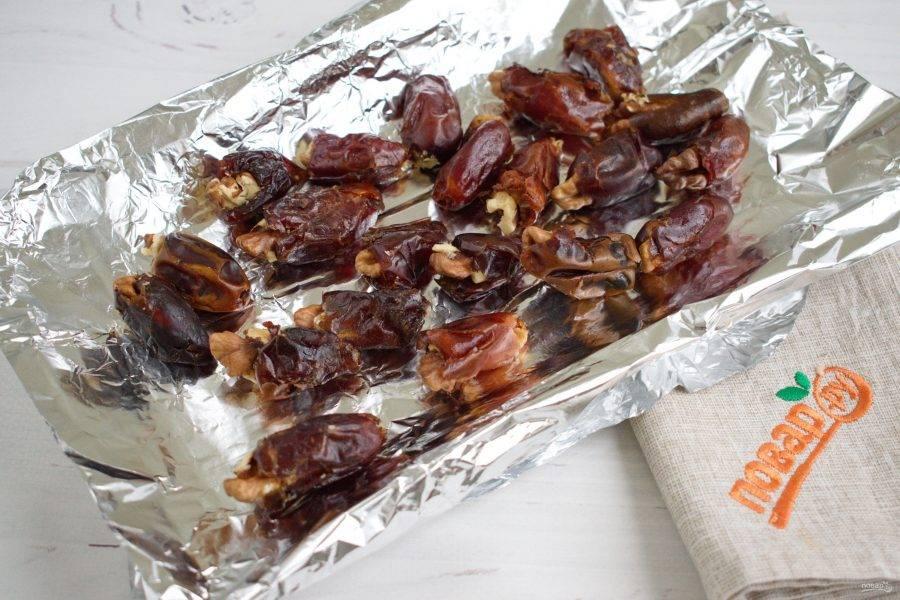 Ядра грецкого ореха разделите на четвертинки. Финики начините орехами. Оставшиеся орехи измельчите.