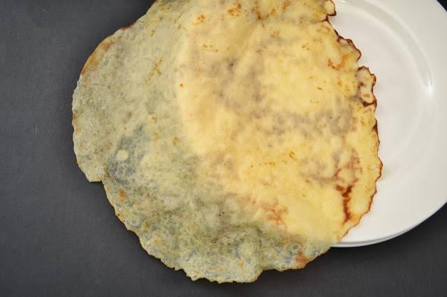 2. Блины получатся тонкие, сложите их горкой. Капусту надо вывалить в глубокую сковороду, добавить лавровый лист и тушить на маленьком огне 30 минут. Лук почистите и нарежьте кубиком, обжарьте на масле до мягкости. Грибы залейте водой и поставьте вариться на полчаса. Через полчаса грибы вместе с бульоном добавьте в капусту, прогрейте.