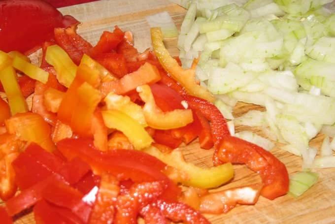 Мелко нарежьте лук репчатый и перец болгарский.