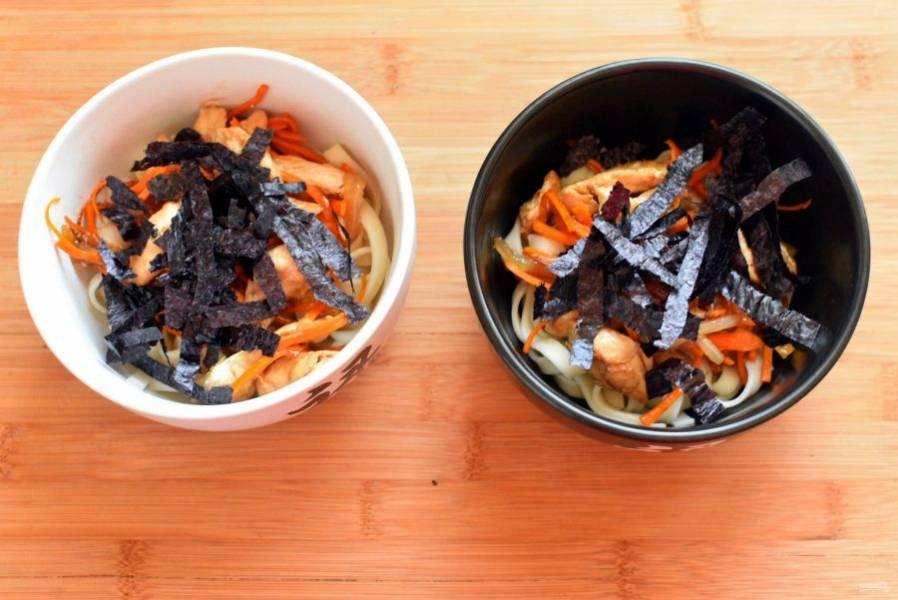 Разложите по глубоким мискам лапшу, сверху выложите курицу с овощами. Затем добавьте водоросли нори, нарезанные широкой соломкой. Резать их удобно ножницами. При желании водоросли можно замочить минут на 5-10 в теплом бульоне.