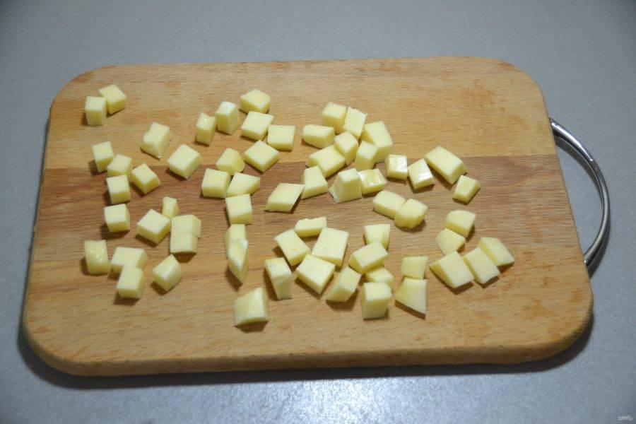 Пока выпекается основа, порежьте кубиком моцареллу.