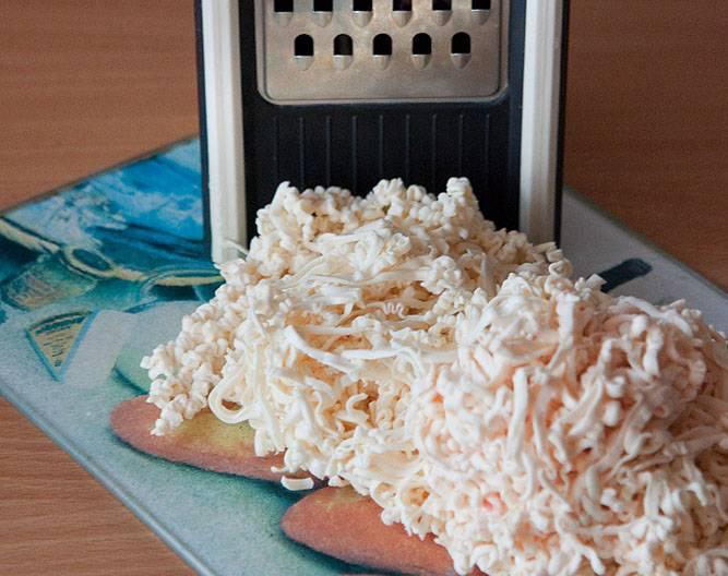 Плавленный сыр натрите на терке. Добавьте в кипящий бульон.