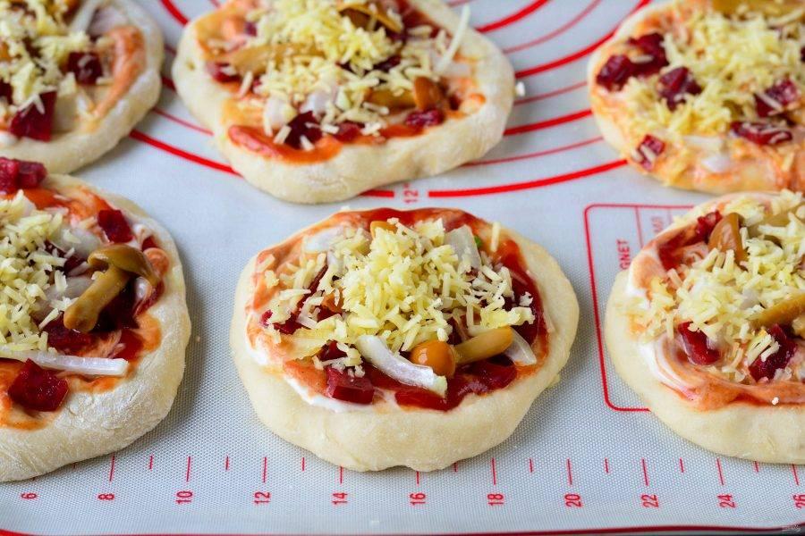 Присыпьте мини-пиццу тертым сыром и поставьте запекаться в разогретую до 200 градусов духовку.