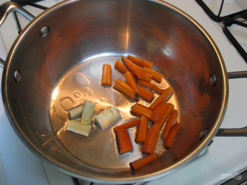 Очищенную морковь нарежьте небольшими кусочками, так же поступите и с корнем петрушки. В глубокую кастрюлю налейте небольшое количество растительного масла, отправьте туда обжариваться овощи.