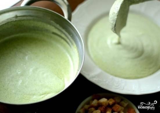 Нарежьте сыр небольшими кусочками и добавьте в кастрюлю. Ещё раз измельчите всё блендером. Суп доведите до кипения и варите 5 минут.