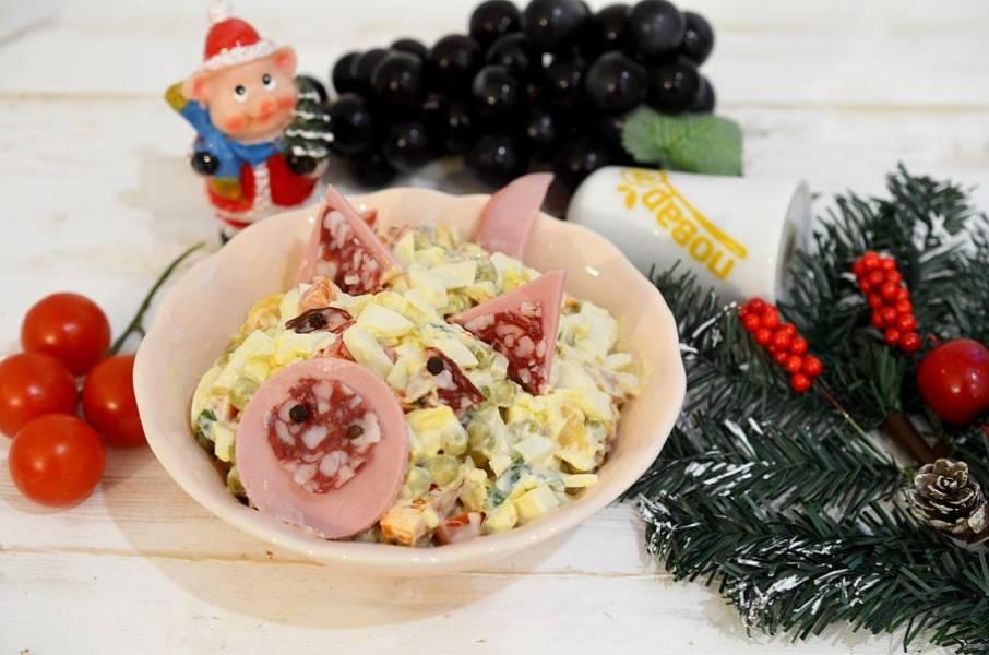 Оформите салат в виде поросенка. Из вареной и копченой колбасы сделайте пятачок, ушки из перца горошком, - ноздри и глаза. Приятного аппетита!