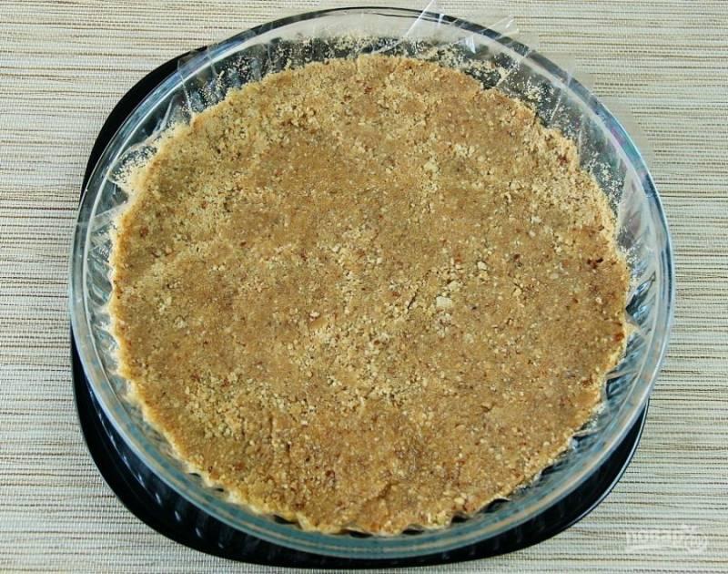 Масло влейте к печенью с орехами. Перемешайте тесто. Утрамбуйте его. Уберите основу торта в холодильник на 1,5 часа.