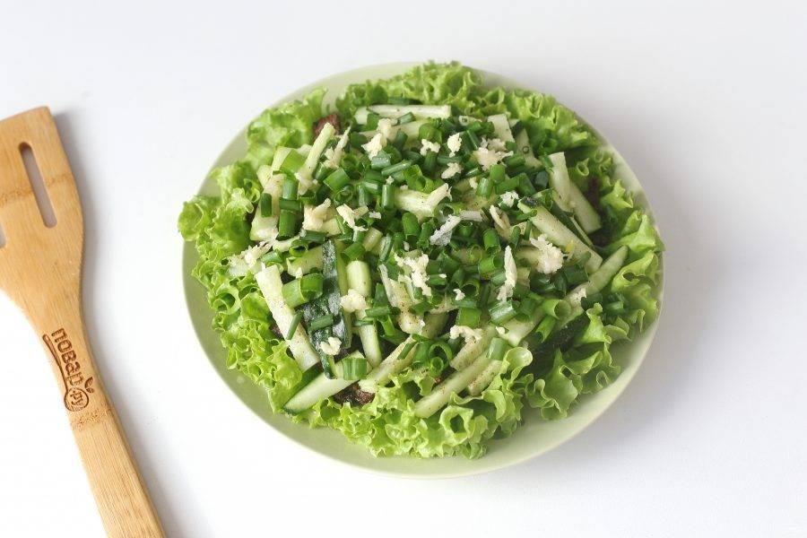Посыпьте огурцы нарезанным зеленым луком и давленным чесноком.
