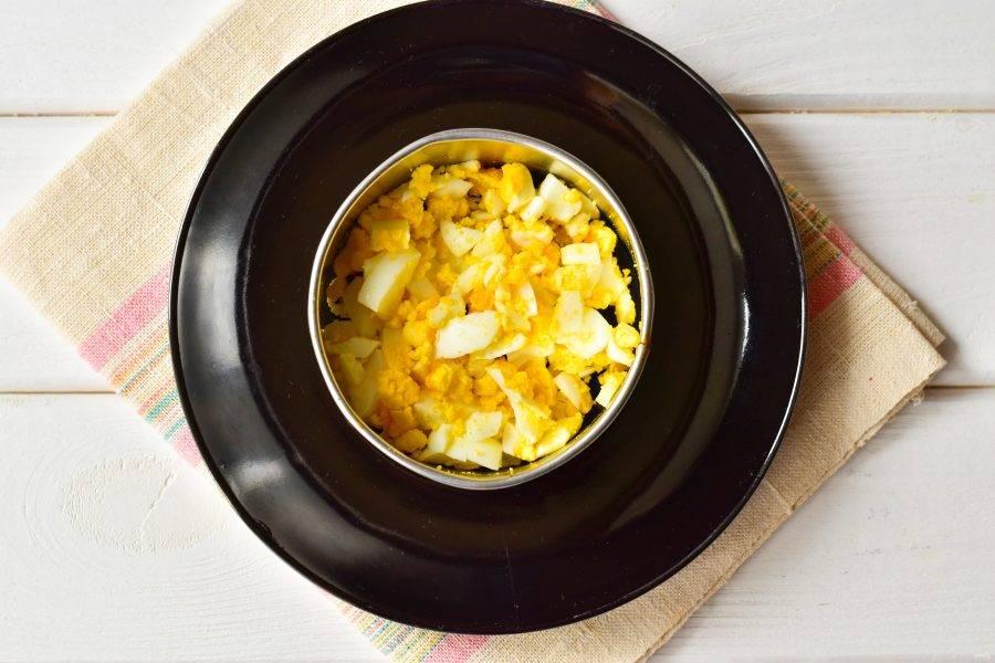 На блюдо установите сервировочное кольцо, выложите яйца, смажьте майонезом.
