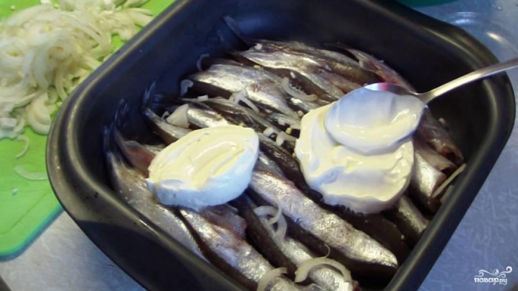 Рыбку выкладываем (в один ряд) в смазанную маслом форму для выпекания. Посолить, поперчить рыбу и хорошенько смазать сметаной (2-3 ст. ложки).