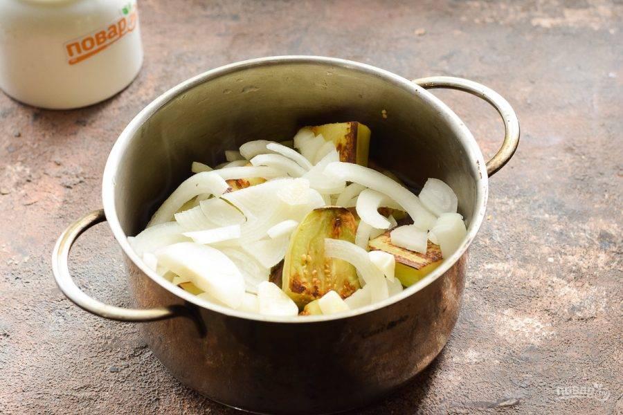 Выложите баклажаны, лук и чеснок в кастрюлю. Перемешайте ингредиенты.