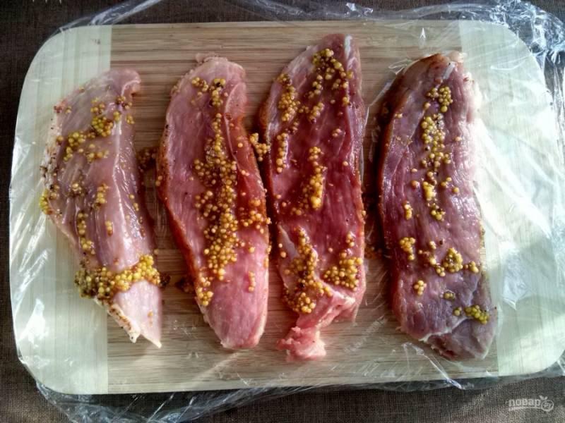 Мясо порежьте ломтиками толщиной в 1 см. Смешайте горчицу и 1 ст.л. оливкового масла, смажьте мясо.