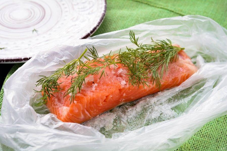 Сверху на рыбу выложите несколько веточек укропа для аромата.