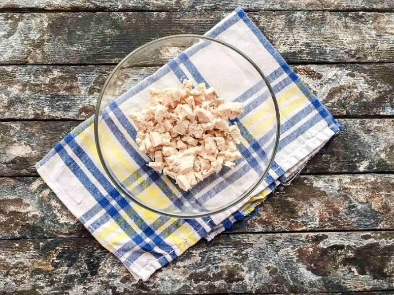 Филе курицы отварите в подсоленной воде, дайте ей полностью остыть, нарежьте небольшими кусочками и выложите в глубокую тарелку.