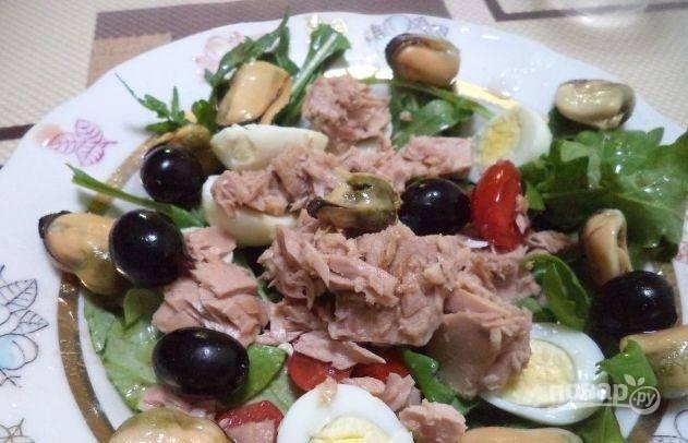 Возьмите большую тарелку для подачи, выложите на нее листья салата. На них положите тунца, оливки и мидии, с которых нужно предварительно слить лишнюю жидкость. Также добавьте нарезанные томаты и перепелиные яйца. Поперчите, посолите и полейте салат оливковым маслом.