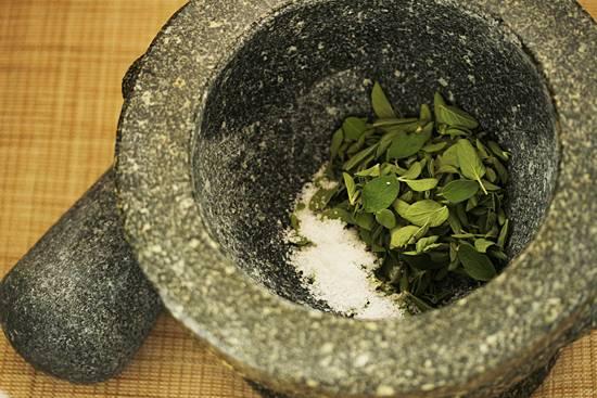 2. Очень важно использовать ступку, ведь именно так вы получите нужную консистенцию и аромат. Небольшими порциями отправляйте туда листочки, насыпьте соль, и начните толочь.