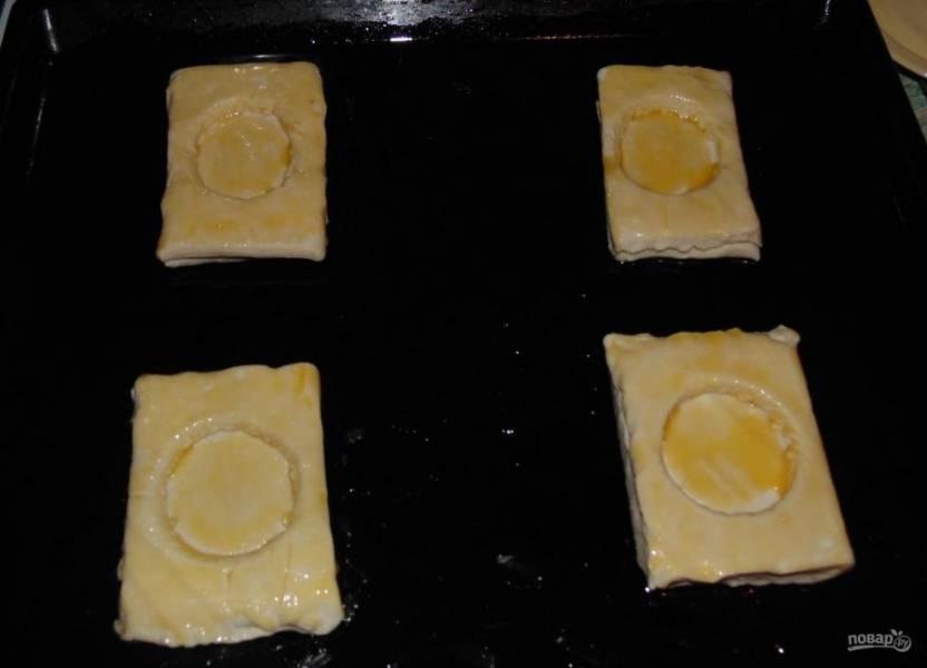 2.Слоеное тесто разрежьте на 8 прямоугольников, у половины по центру с помощью рюмки вырежьте круг. Уложите прямоугольник с кругом наверх прямоугольников без круга. Смажьте каждый яйцом.