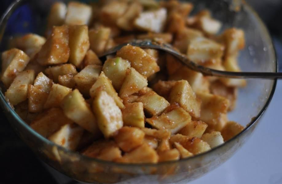 Приготовим начинку. Яблоки промываем и нарезаем кубиками, удалив сердцевину. Добавляем корицу, мускатный орех, 100 граммов карамели и лимонный сок. Перемешиваем.