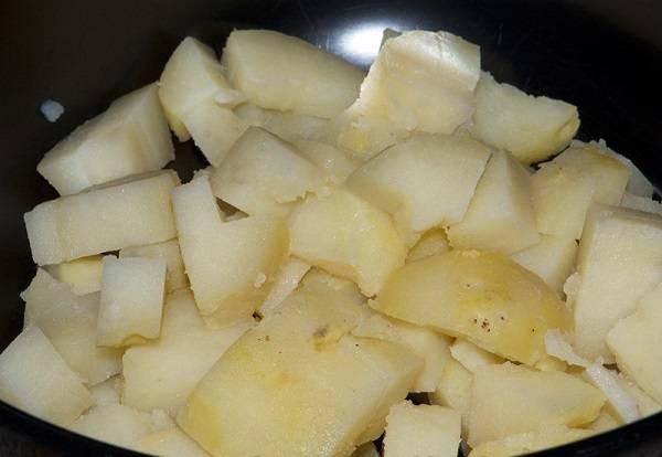 1. Первым делом нужно вымыть картофель и отправить его варить до готовности. Затем как следует остудить, очистить и нарезать средними кусочками. Картофель делает салат более сытным, но при желании его можно исключить.