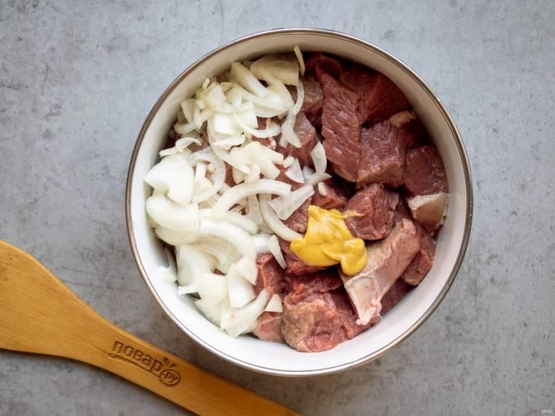 Лосятину до приготовления рекомендуется вымочить 10-12 часов в воде или же замариновать. В данном рецепте предлагаю замариновать мясо, чтобы получить богатый вкус и аромат. Нарежьте мясо кусочками, добавьте горчицу, нарезанный полукольцами лук.