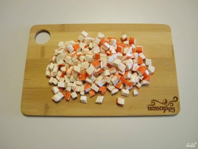 Крабовые палочки порежьте кубиками такого же размера, как и яйца.