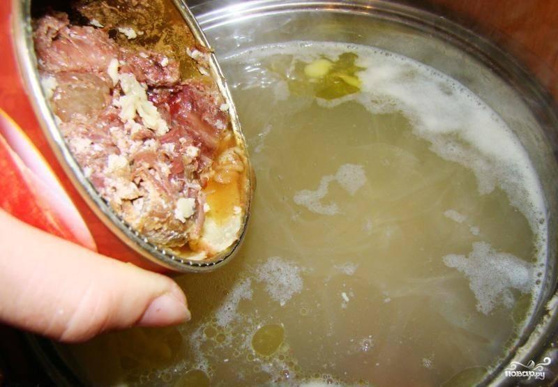 4. Сразу после овощей добавьте тушенку, перемешайте содержимое кастрюли, доведите до кипения и уменьшите огонь (сделайте его минимальным).