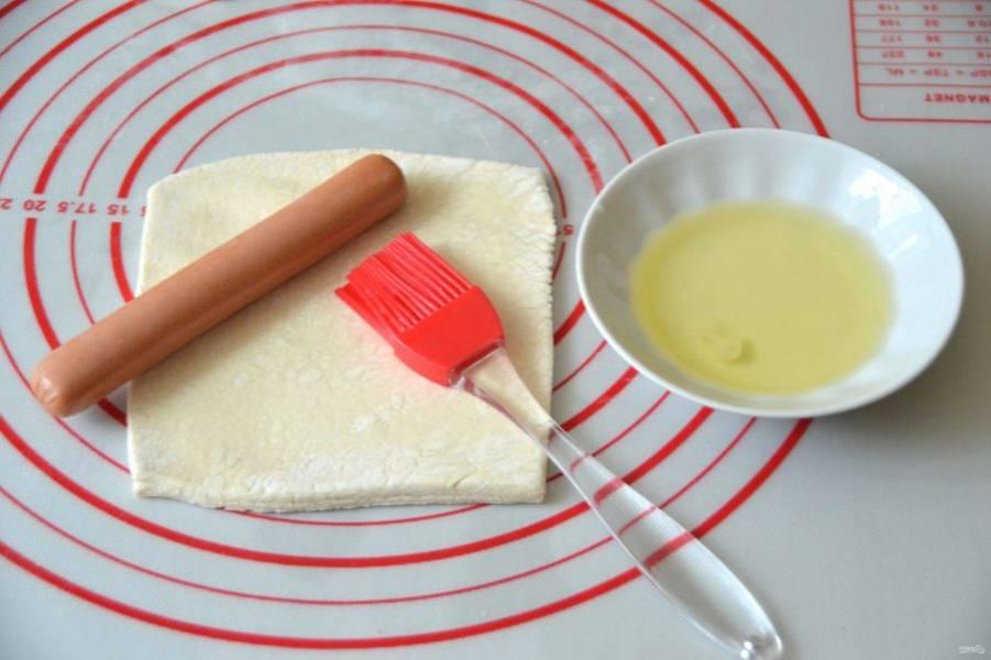 Раскатайте тесто до размера сосиски, смажьте яичным белком.
