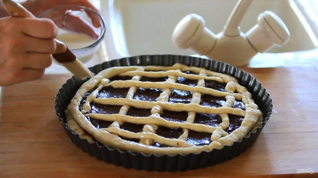 6. Из остального теста сделайте трубочки. Покройте ими пирог, образуя узор в виде сеточки. Смажьте тесто молоком и посыпьте сахаром.