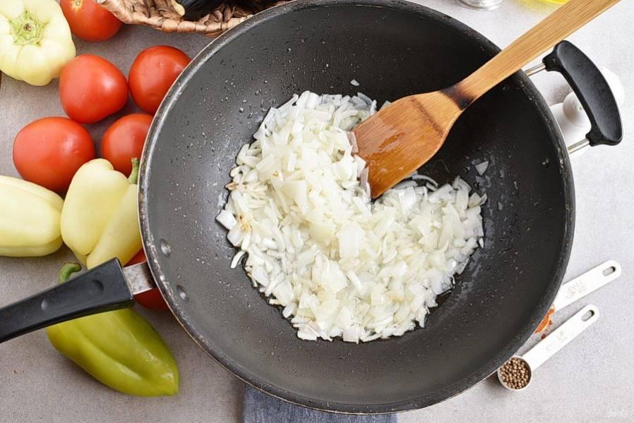 Возьмите глубокую просторную сковороду или казан. Лук нашинкуйте кубиками и обжарьте в трех столовых ложках масла до полупрозрачности на среднем огне.