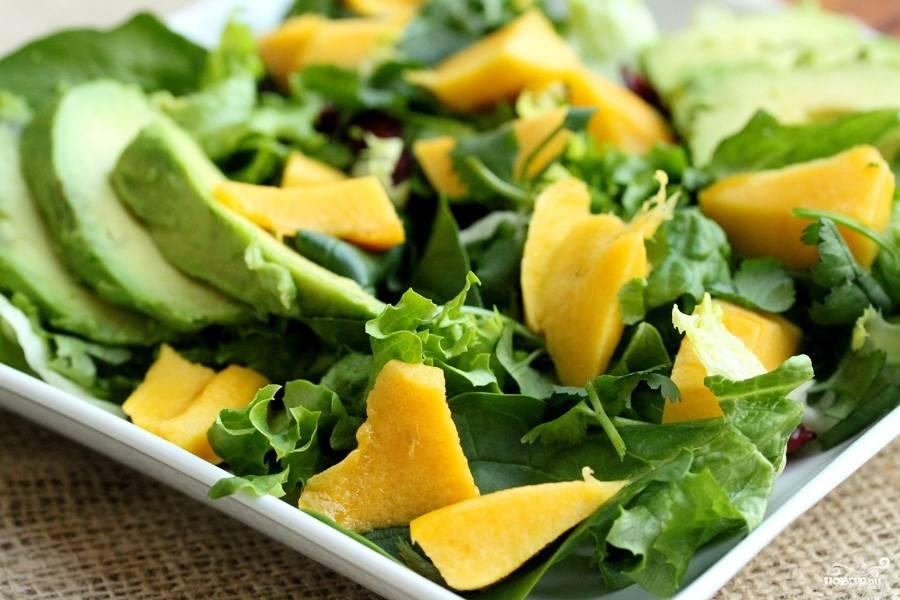3. Все зеленые компоненты - латук, шпинат, кинзу - моем и рвем руками. Выкладываем на дно салатницы, посыпаем клюквой. Добавим кусочки манго и авокадо. Наверх уже выкладываем креветки и жареные орешки. Заливаем маслом со специями, это и есть заправка салата.