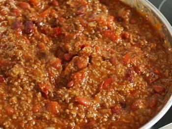 Добавляем по очередности в сковороду помидоры, размешиваем их там же до состояния пюре, добавляем пюре из фасоли, размешиваем и, наконец, добавляем вторую целую половину фасоли. Посыпаем содержимое сковородки специями, которые у нас есть и перемешиваем. В последнюю очередь добавляем тертого сыра.