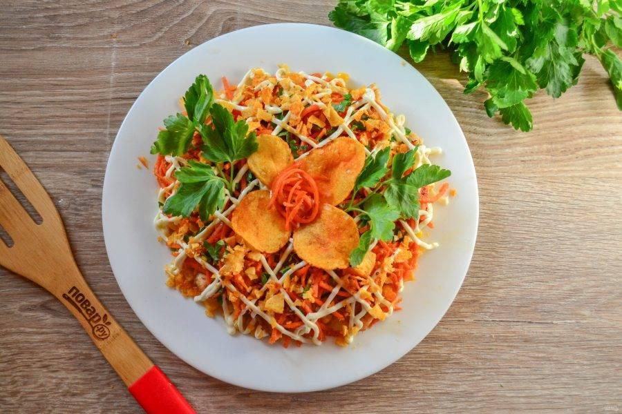 Покройте салат сеточкой майонеза и присыпьте крошкой из чипсов. Украсьте салат зеленью и подавайте к столу.