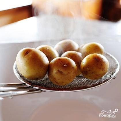 2. Слить воду, разрезать картофель пополам и поместить в миску.