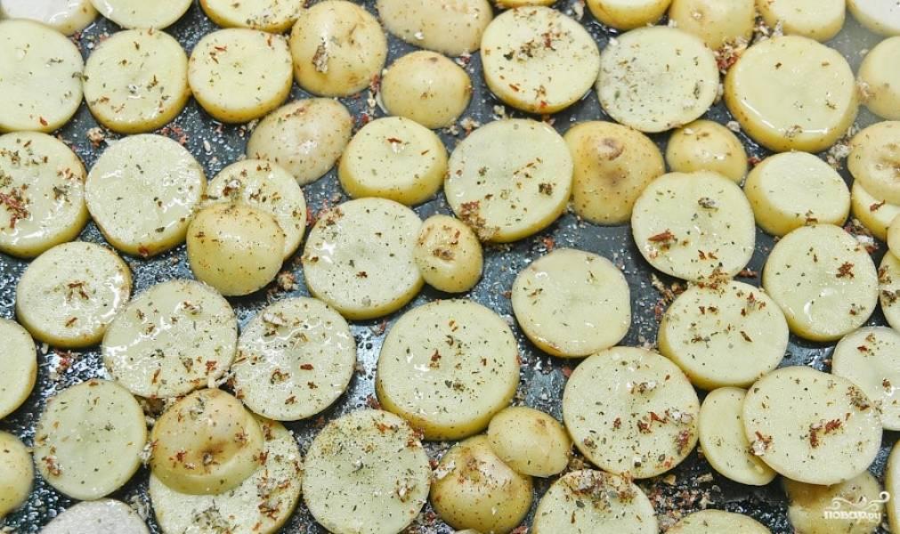 3. Разогрейте духовку до 220 градусов. На противень выложите кружочки картофеля. Сверху равномерно распределите часть чеснока. Посолите. Присыпьте любимой приправой. Слегка спрысните постным маслом. Отправьте в духовку. Запекайте 15 минут.