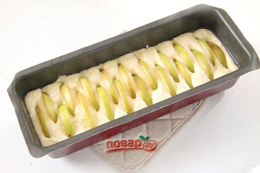 Тесто переложите в смазанную маслом форму для выпечки. Сверху воткните в тесто нарезанные груши. Они должны лишь слега выглядывать из него.