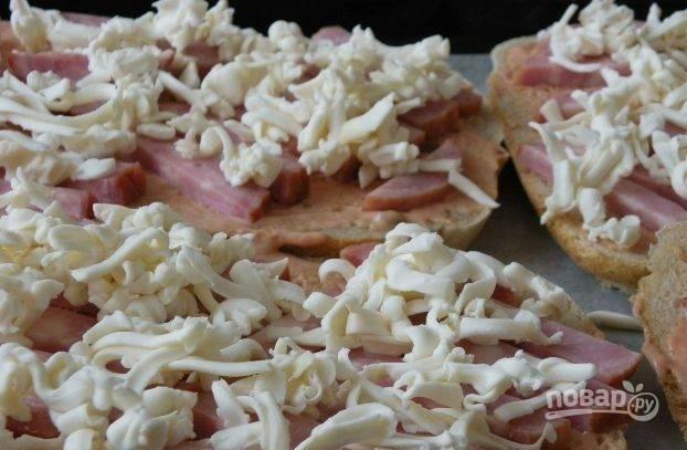 В завершение посыпьте ветчину тертым плавленым сыром. Положите хлеб на противень и поставьте его в духовку, разогретую до двухсот градусов. Выпекайте пиццу десять-пятнадцать минут. При подаче посыпьте рубленой зеленью.