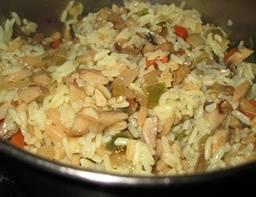 Чтобы из шампиньонов выпарилась жидкость, нужно примерно 10-12 минут. Теперь добавим остальные специи, перемешаем. Вы видите, что овощи пустили сок - самое время добавить риса. Через пару минут перемешивания заливаем в казан воду и накрываем крышкой. Тушим в течение 15 минут на медленном огне. Плов готов.