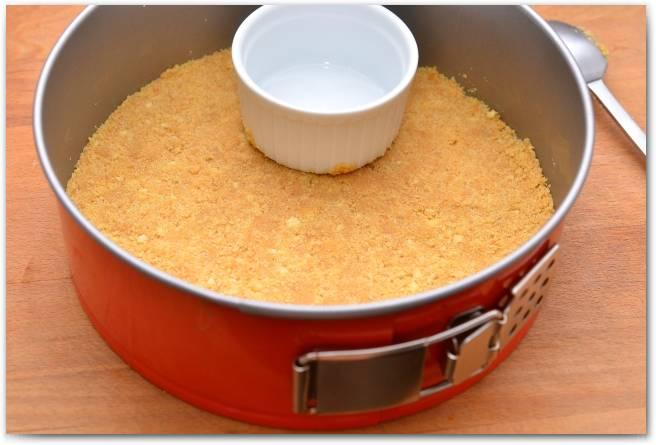 Кладем печенье в форму и утрамбовываем, равномерно распределяя его по поверхности. Ставим замерзать в холодильник.