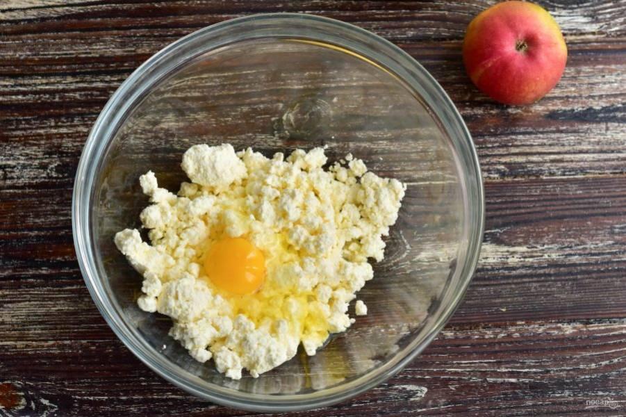 В миску выложите творог. Вбейте к нему яйцо.