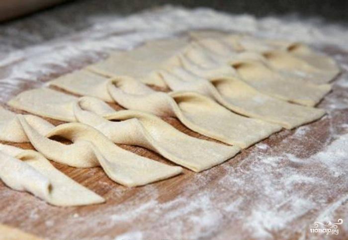 Охлаждённое тесто нужно раскатать слоем около четырёх миллиметров. Затем получившийся пласт надо нарезать на полоски шириной около пяти сантиметров. В каждой полоске нужно сделать надрез посередине. Выверните тесто через этот надрез.