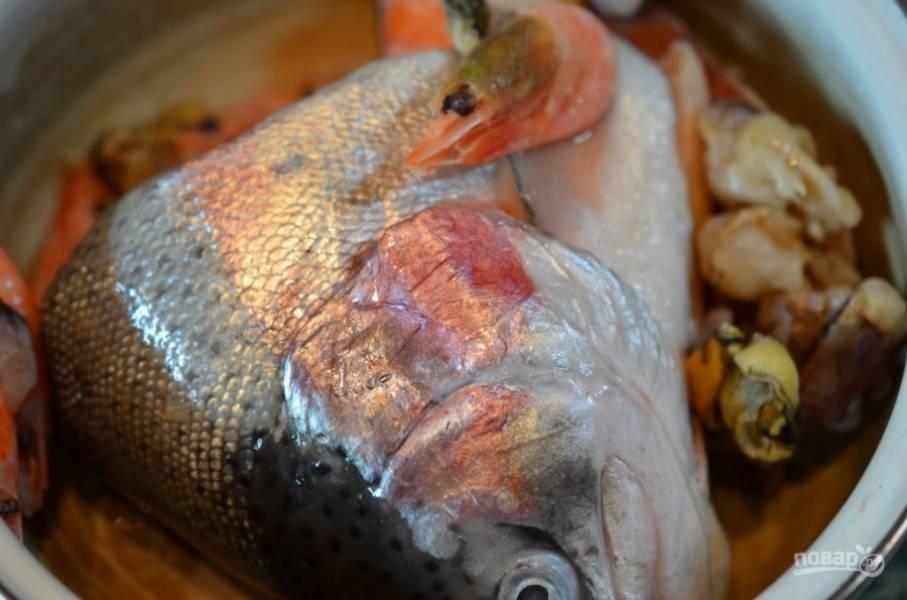 Головы и рыбные обрезы хорошо промойте. Обязательно удалите жабры. Залейте холодной водой. После закипания удалите пену и варите рыбный бульон на очень маленьком огне 30 минут. Остудите головы. Выберите мясо. Бульон процедите.
