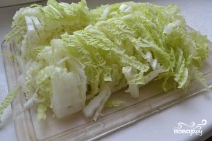 Пекинскую капусту нарезать на полоски, слегка обмять руками.