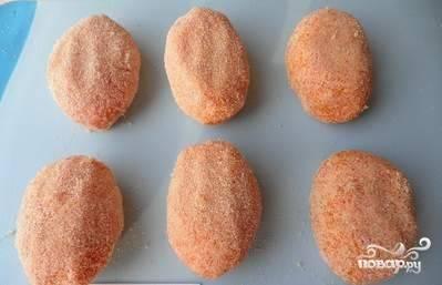 Формируем из получившейся массы небольшие котлетки, обваливаем их в манной крупе.