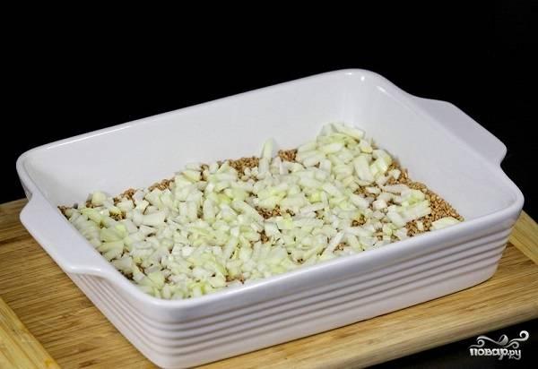 2. Очистите луковицу, нарежьте её мелкими кубиками. Выложите ровным слоем поверх крупы.