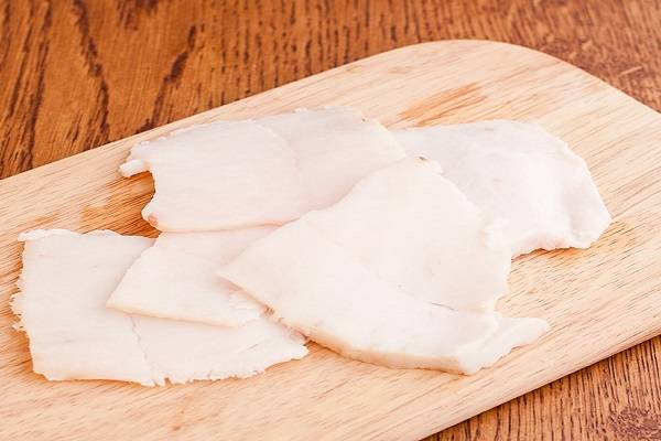2. Сало, предварительно отправив его в морозилку на 7-10 минут, нарежьте тонкими ломтиками по размеру картофеля. Можно использовать также сало с мясной прослойкой, это придаст картошке интересный аромат.