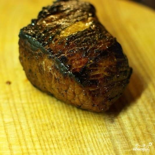 """Обжаренный кусок мяса кладем в форму для запекания и ставим в духовку, разогретую до 190 градусов. Теперь самое сложное - не пересушить мясо. Точное время запекания мяса зависит от величины куска и от того, какую степень готовности предпочитаете. В среднем, кусок говядины весом 400 граммов нужно запекать около 10 минут при 190 градусах. Затем кусок мяса достаем и даем ему 10 минут постоять. Ни в коем случае не нарезаем! Мясо еще горячее, температура внутри него высокая, потому мясо будет """"доходить"""" до готовности самостоятельно."""