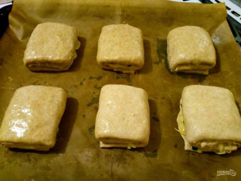 Разместите на подготовленном противне постные слоёные пирожки с кольраби и выпекайте их в разогретой до 190-200 градусов духовке в течение 40-45 минут.