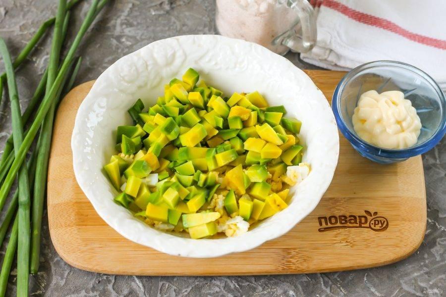 Половину авокадо очистите от кожуры, удалите ядро. Нарежьте мякоть мелким кубиком. Если не будете заправлять паштет майонезом, то замените его лимонным соком, иначе нарезка авокадо потемнеет.